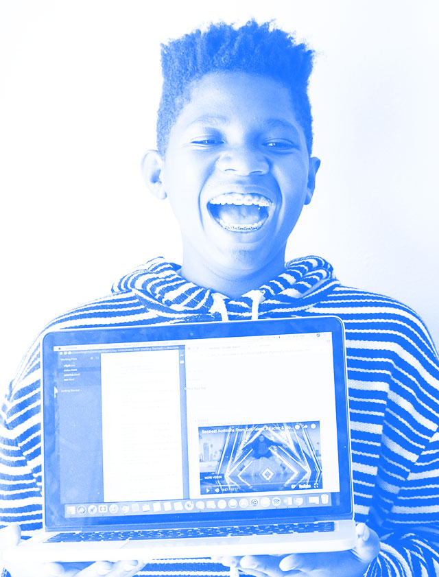 Elijah smiling with his laptop displaying the website he built.